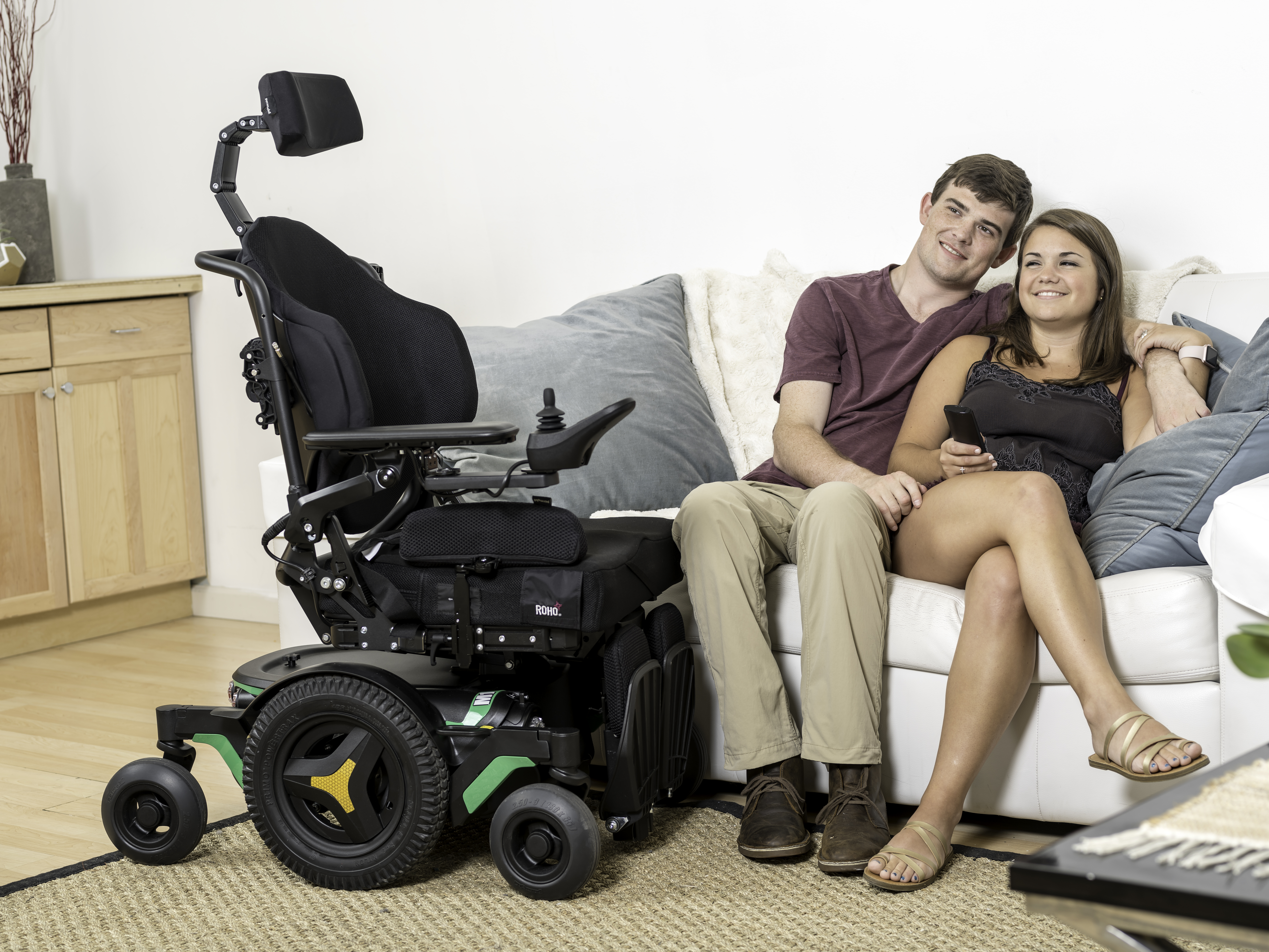 M1 indoor powerchair clinical mobility solutions parked next to a couple sitting on a sofa